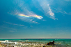 The rainbow  at The rocky coast  overlooking the turquoise blue. Sea in warm summer day. Greece. Halkidiki Stock Image