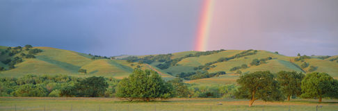 Rainbow and rolling hills i. N central California Stock Photo