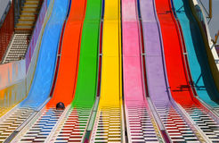 Rainbow Runner. A baseball cap sits at the bottom of a rainbow-colored carnival slide at the county fair Stock Image