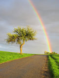 Rainbows end. Beautiful view on rainy and sunny landscape stock image