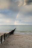 Rainbow at sea. Rainbow arcing from heavy cloud to the ocean Royalty Free Stock Image