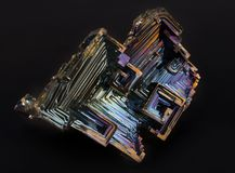 Shiny colorful mineral bismuth on a dark background. Rainbow shiny colorful mineral bismuth closeup macro on a dark background Royalty Free Stock Images