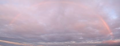 Rainbow Sky. This is a panoramic shot of an entire rainbow at sunset in a dramatic sk stock photo