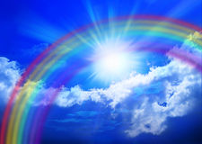 Rainbow Sky. A rainbow in a blue sky with clouds and sunbeams