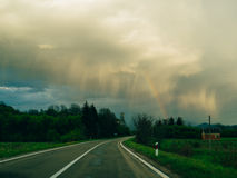 Rainbow in the sky above church and road. Rainbow in the sky above the church and road Stock Images
