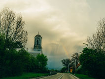 Rainbow in the sky above church and road. Rainbow in the sky above the church and road Stock Image