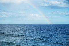Rainbow in the sky, above the ocean. A view of a rainbow in the sky, above the ocean, after a storm Stock Image