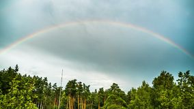 Rainbow in the sky above the trees. Timelapse. Colorful rainbow in the clouds moves in the sky stock video footage