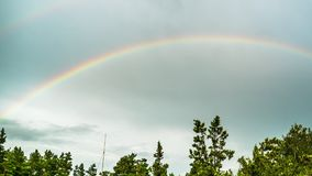 Rainbow in the sky above the trees. Timelapse. Colorful rainbow in the clouds moves in the sky stock footage