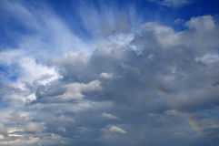 Rainbow in the sky with beautiful cloud. Picture shows saturated and colorful rainbow under beautiful cloud in the sky over lake's surface stock photo