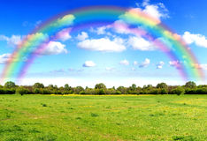 Rainbow sky clouds and grass on meadow Stock Images