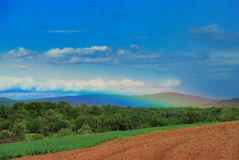 Rainbow sky clouds mountains and meadow Stock Image