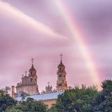 Rainbow in the sky near the church Stock Photography