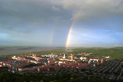 Rainbow small city. After the heavy rain over the rainbow appears small city Stock Images