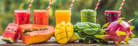 Rainbow from smoothies. Watermelon, papaya, mango, spinach and dragon fruit. Smoothies, juices, beverages, drinks variety with fre. Sh fruits on a wooden table stock photo