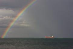 Rainbow sopra il mare I raggi del ` s del sole illuminano la nave Fotografia Stock Libera da Diritti