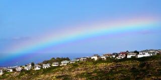 Rainbow sopra le case di vista di oceano Fotografie Stock