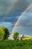 Rainbow sopra un campo dell'azienda agricola Immagine Stock