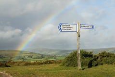 Rainbow sopra un signpost con le destinazioni, Regno Unito. Fotografia Stock Libera da Diritti