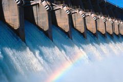 Rainbow in spillway. Water flowing from the open spillway with a rainbow in the mist royalty free stock image