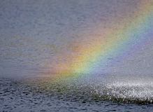 Rainbow in the spray Stock Images