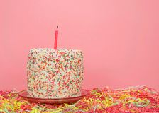 Rainbow sprinkle cake on pate with confetti below royalty free stock photo