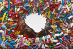 Rainbow sprinkles on doughnut close-up Stock Photo