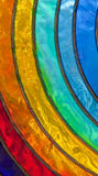 Rainbow stained-glass. A close-up photograph of a rainbow coloured stained-glass. The glass is imperfect and has un-even texture stock images