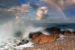 Rainbow during the storm. A violent storm on the horizon was rain, waves crashed on shore. Above the horizon hung a rainbow Royalty Free Stock Photography
