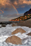 Rainbow during the storm. A violent storm on the horizon was rain, waves crashed on shore. Above the horizon hung a rainbow Royalty Free Stock Photo