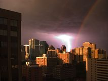 Rainbow Storm. A bolt of lightning caught amidst a sky featuring a rainbow over Edmonton, Alberta stock images