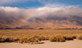 Rainbow Storm Brewing Rain Falling Sierra Nevada Range. Clouds hug the Sieera Nevada Range tight as a rainbow forms in the mist Stock Image