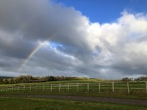 Rainbow, storm clouds and blue sky over rural landscape stock photo