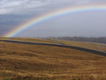Rainbow and stormy clouds. Beautiful rainbow and stormy clouds above. Dry grass field with the winding road on the way to Haleakala mountain Maui Hawaii Royalty Free Stock Photo