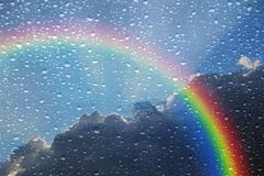 Rainbow stormy clouds sky outside wet window. Photo of a stormy cloudy sky with rainbow arc looking through a wet window stock images