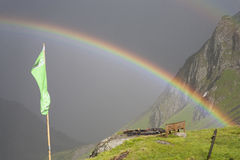 Rainbow stretching over a mountain valley in front of dark thunder storm. Stock Photos