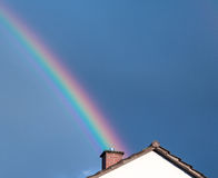 Rainbow after a summer thunderstorm on a summer evening. Perspective, shining into or out of a a chimny, top of house roof, facade Stock Photography