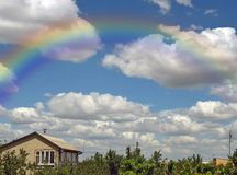 Rainbow and summers cloudy sky Royalty Free Stock Image