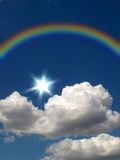 Rainbow, sun and cloud. Rainbow, sun and white fluffy cloud on a background of the dark blue sky Stock Image
