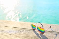 Rainbow Sunglasses lying on a wooden decking.  stock photos