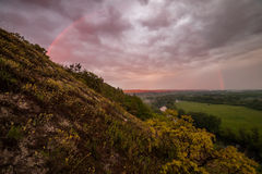 Rainbow on Sunrise over Valley Stock Photo