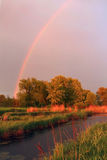 Rainbow at sunset. Over the small river Stock Images