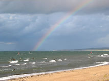 Rainbow surfing. Surfers under a rainbow after the storm Stock Images