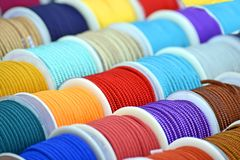 Rainbow textile cord coils pack heap on the wall, industry strings diversity,. Rainbow textile cord coils pack heap on the wall, modern industry strings stock photo