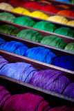 Rainbow threads. Close-up on colourful thread reels in a haberdashery shop arranged in a rainbow sequence. Selective focus on indigo Royalty Free Stock Photo