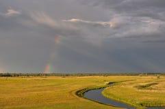 Rainbow after a thunderstorm at sunset. Stock Photos