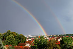Rainbow in a town. This small town is located in the west of the Czech Republic, Europe. A beautiful rainbow, painted in the sky, is decorating typical local stock photo