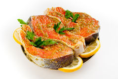 Rainbow trout. Stake from an rainbow trout in marinade with a lemon and fresh greens on a plate stock photos