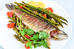 Rainbow trout with asparagus and cherry tomatoes royalty free stock photos