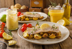 Rainbow trout fillet with roasted potatoes. Baked rainbow trout with roasted potatoes and homemade mayonnaise Royalty Free Stock Images